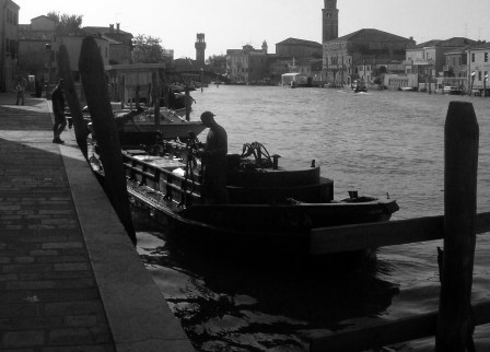 black and white silhouette of boat on canal in Venice