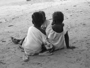 Three Gambian children sit on the ground waiting for a village meeting.