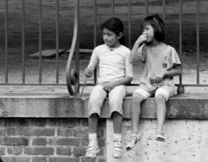 A boy and a girl, about 10 years old, dangle their feet over the ledge of an elevated walkway through a city park.