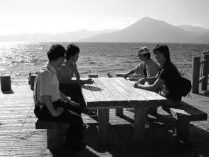 Four Japanese boys sit at a picnic table by a beach talking.