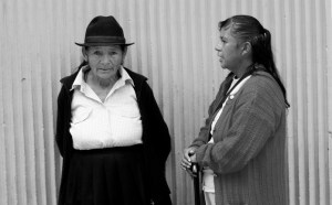 Two middle-aged Latina women in conversation, a blank wall behind them.