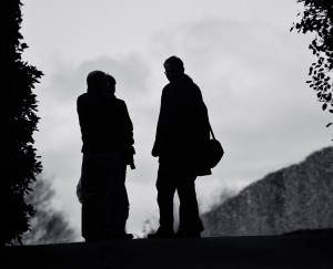 Three people chatting beneath a cloudy sky