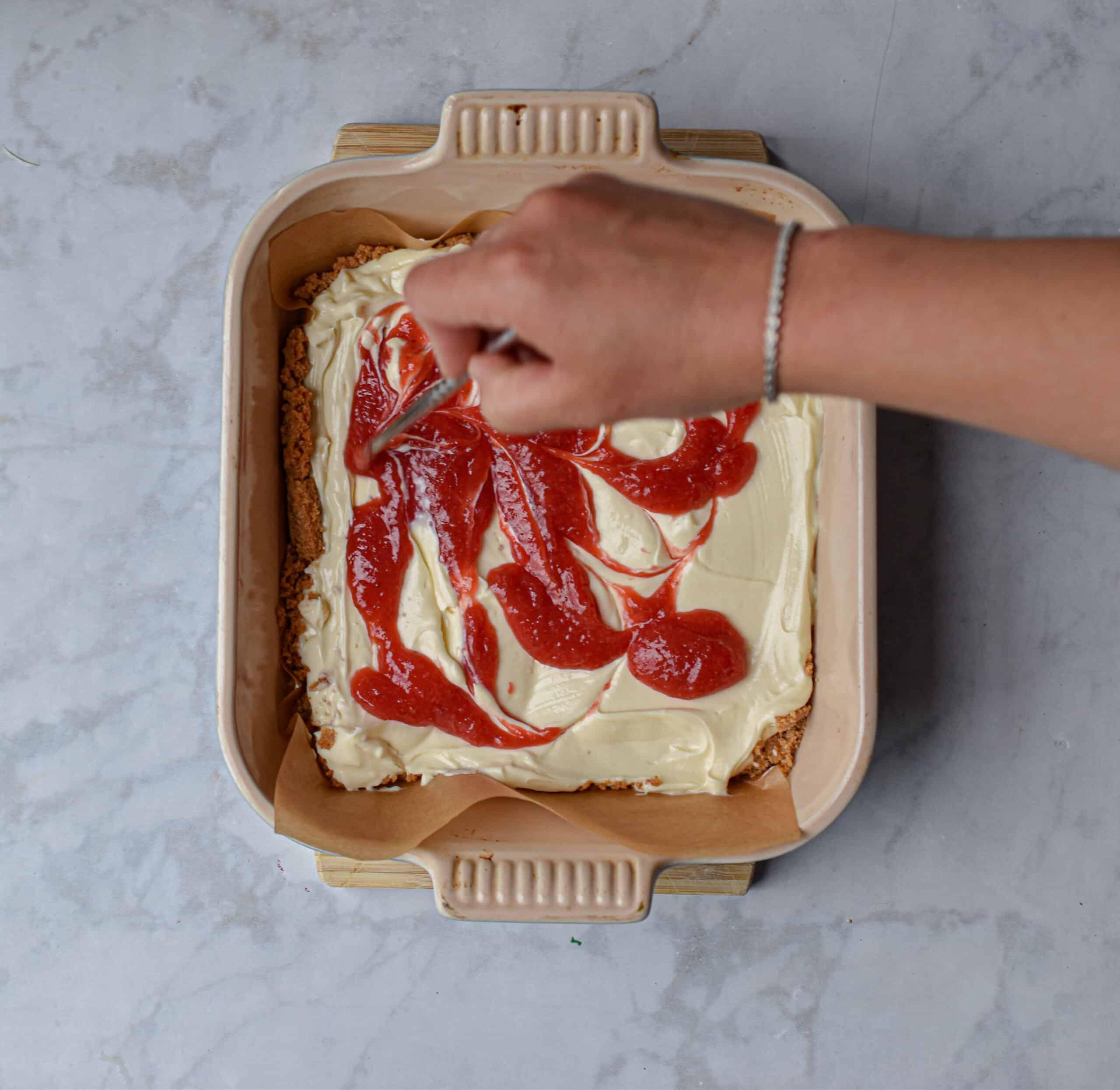 Swirl the strawberry puree into the cheesecake mixture