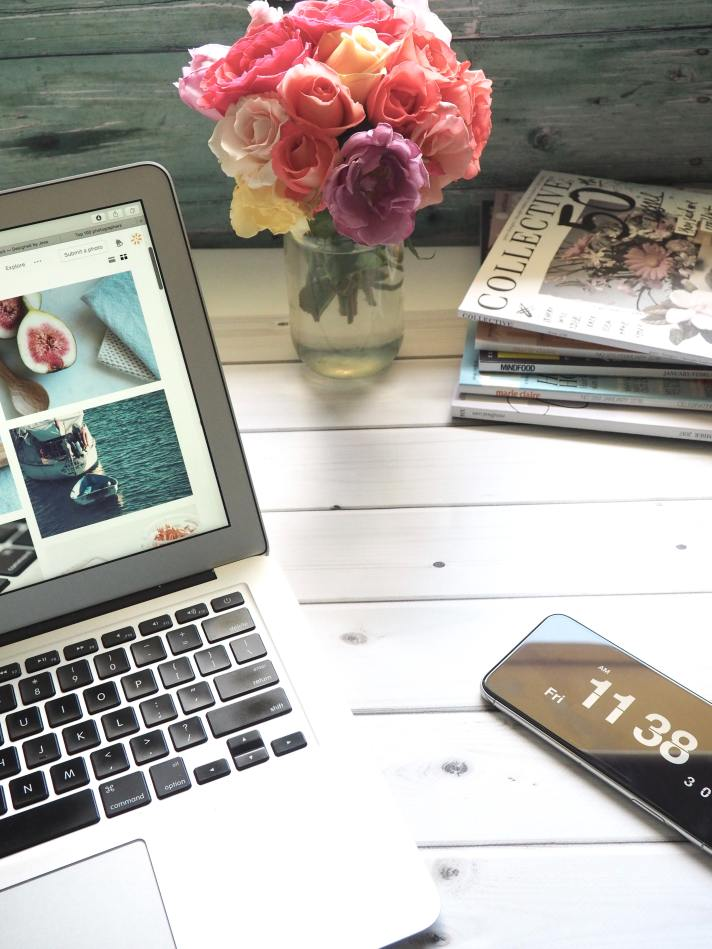 A laptop is shown on a desk alongside a phone, flowers in a vase, and a collection of magazines.