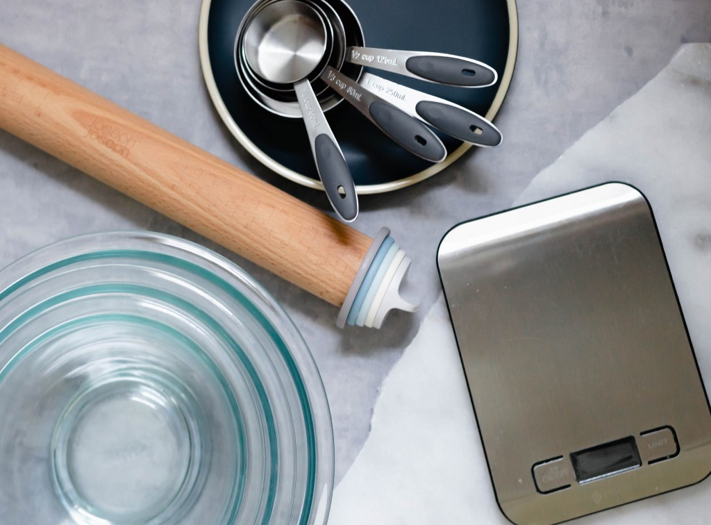 measuring cup rolling pin food scale and pyrex bowls on a flatlay