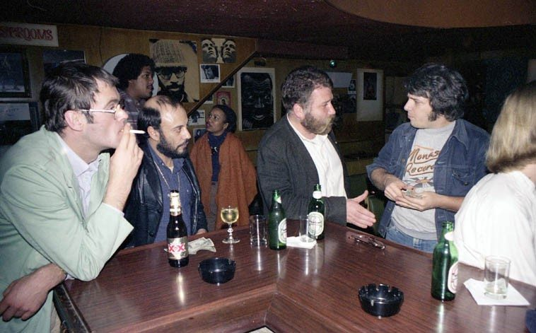 The late Hans Reichel, table-top guitarist (w/ cigarette) at the bar with Harry Miller, while  Peter Brotzmann & Vinny Golia discuss intergalactic sonic convergences -- I see flutist  James Newton in rear,  and on extreme right that might be Alex Cline ---- The Lighthouse,  Hermosa Beach, California ---- December 3, 1980 ------ everybody convened to catch Horace  Tapscott Quintet (David Bryant & Roberto Miranda, basses; Gary Bias, alto sax; Fritz Wise, drums)