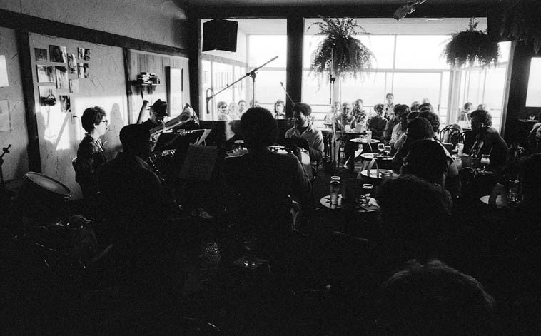 James Newton Wind Quintet @ Pasquales, Malibu ---- September 28, 1980. John Nunez, bassoon; James, flute; Red Callendar, tuba; John Carter, clarinet; Charlies Owens, oboe & English horn; (Allan Iwohara was on koto on this date as well) ---- photo by Mark Weber ----- James Newton & family live in Corrales, New Mexico, just over the Rio Grande from Albuquerque ---- Pasquales was right on the beach and that is the setting sun coming in over the Pacific in this shot ---- you can see Buddy Collette in the audience