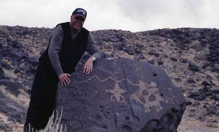 """John Betsch with Star beings (only known to exist in Rio Grande Valley petroglyphs) and a migration symbol and a talking dog ------ March 20, 2000 --- photo by Mark Weber ---- we were laughing because JJ had just seen his first cholla (cactus) and exclaimed """"Sacrebleu! what's this?"""""""