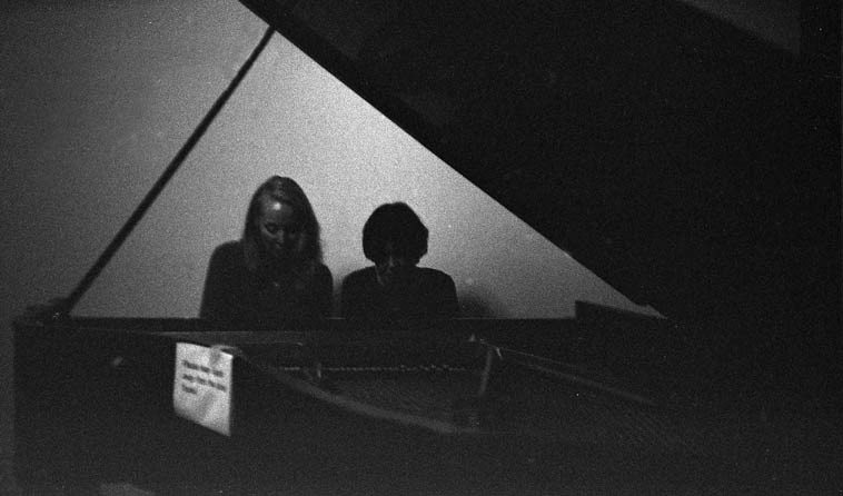 Kazzrie Jaxen & Virg Dzurinko, four-handed piano -- November 16, 2o14 -- This photo is about the same quality as the one surviving picture of Lincoln at Gettysburg, and that's because (here comes the excuses) the camera I use with flash was out of film and the light was very gray at this very end of the evening -- photo by Mark Weber with Olympus RC-35 rangefinder