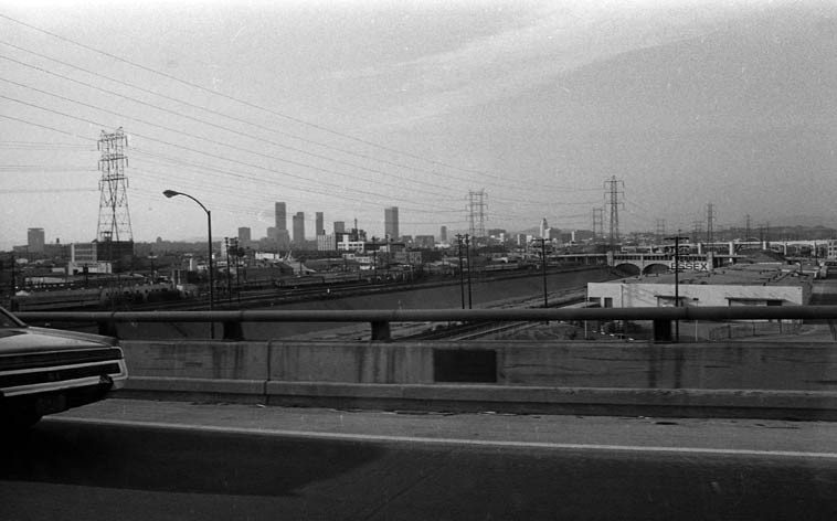 Fred Voss is a poet of Los Angeles ----- photo by Mark Weber shot from moving car on Santa Monica  Freeway looking northwest across L.A. River toward downtown -- October 26, 1980