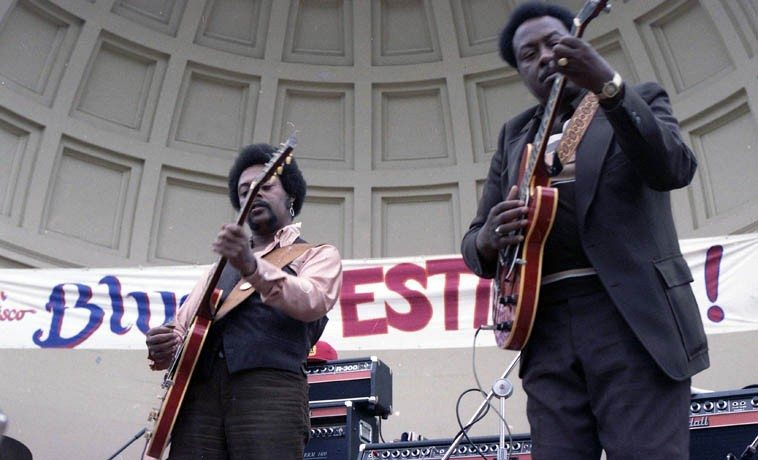 """Luther Tucker & Jimmy Rogers -- San Francisco Blues Festival -- Sunday August 12, 1979 -- Luther Tucker was a protoge of Robert Lockwood Jr and with Lockwood both were members of Little Walter's band for seven years ---- Jimmy Rogers was a member of the Aces and broke open the electric guitar as the post-war driving machine ----  Here's what happen'd: There had been a recording ban (and shortage of shellac) during World War II  but with the end of the war in 1945 and the lifting of the Petrillo Recording Ban the curtain went up and things had changed in a great big way: Charlie Parker and bebop was revealed in NYC, and in Chicago Muddy Waters blasted forth with the Aces backing him up -- I happen'd to be backstage standing around with Stevie Ray Vaughan when the van pulled up driven by festival organizer Tom Mazzolini that had both Luther and Jimmy arriving,  I had been at the festival the day before so knew what Jimmy Rogers looked like and said to Stevie: """"That's Jimmy Rogers,"""" and he was awestruck, """"That's Jimmy Rogers?"""" in a reverent hushed whisper, because he knew what Jimmy Rogers stands for ---- photo by Mark Weber"""