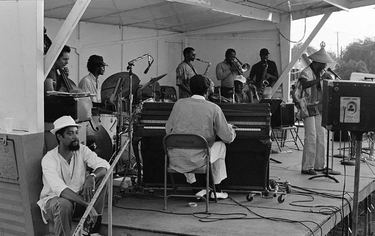 Horace Tapscott & Pan Afrikan Peoples Arkestra ---- Watts Towers Jazz Festival -- July 16, 1983 ----  Dadesi Komolafe flute solo w/ strings: Melvin Moore, violin; David Bryant & Roberto Miranda, basses;  Larry Gales, cello; poet Kamau Daaood sitting on steps; saxes: Ernie Roberts, Gary Bias, Dadesi;  Thurman Green, trombone, and I didn't catch the drummer's name -- photo by Mark Weber ---- (David  Bryant is behind Roberto) -- 10-piece ensemble + poet