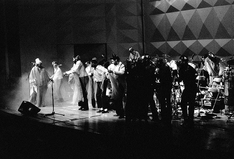 Sun Ra & The Solar Myth Cosmic Jetset Arkestra w/June Tyson, Michael Ray, Marshall Allen,  John Gilmore, Martin Banks -- April 16, 1988 Cleveland, Ohio ---- This was the first time my wife Janet had ever  witnessed Sun Ra:  The large concert hall full audience of about 2,000 at Cuyahoga Community  College opened with the lights going down to near darkness, then a saxophone screeching like a pterodactyl amid horn section chaos, trombone wailing like an elephant,  giant log drum rumblings, you could see smoke (dry ice probably) Then > BANG BANG giant flames erupt  from a pyro device from stage left and right, smoke crawling close to the floor and standing center stage  with that lampshade hat, his arms outstretched, diaphanous robes swirling was SUN RA as the  Arkestra went into full big band intergalactic swinging furious blast-off ---- I looked over at my girlfriend (not  married yet, she still in med school) and her eyes were bugged out!  (Later, backstage when Sun  Ra found out she was a podiatrist he had her check his feet) ---- photo by Mark Weber