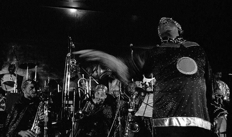 Sun Ra Omniverse Arkestra: Joe Ore, bass; Damon Choice, vibraphone & thunder drum; Steiner, electro-horn; Vincent Chauncey, Fr. horn; Tony Bethel, trombone; Michael Ray, trumpet; Eloe Omoe, bass-clarinet;  Danny Davis, Marshall Allen, John Gilmore, saxophones; June Tyson, vocals & dance; James Jacson,  bassoon; drumsets L to R: Craig Haynes, Lex Humphries, Samarai; Sun Ra, keyboards -- 15-piece band  at Myron's Grand Ballroom -- April 2, 1981 Los Angeles -- photo by Mark Weber ---- also, I believe Luqman  Ali was on percussion this concert because I remember he was a guest on Jay Green's KPFK radio show,  and I seem to recall Jay had something to do with the production of this concert (?)