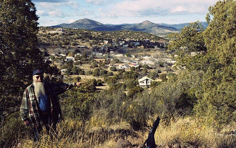 Ken Keppeler on Boston Hill pointing to their home (the 2-story) with the hamlet of Silver City, New Mexico  in the surrounding valley -- February 5, 2008 -- photo by Mark Weber ----- We don't get down to their place too often, it's 5 hours south of Albuquerque but when we do it's evenings out doors around a fire while musicians from all the surrounding hills and backwaters play the old songs . . . . .