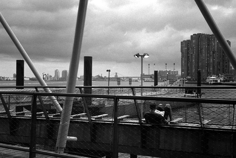 Waiting for the water taxi at 34th Street -- 3:10pm August 23, 2o14 (that's not me in the photo) East River looking south to Williamsburg Bridge on my way to Connie's loft -- photo by Mark Weber