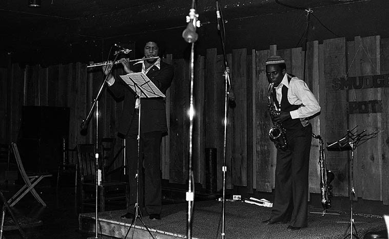 James Newton & David Murray ---- two college guys giving a recital in the basement of the Student Union Building at Claremont Colleges, a little venue called The Smudge Pot ---- January 15, 1977 -- (this is David's alma mater and on this night he was visiting having quietly graduated the year before when he moved to NYC to get into the action on the Loft scene) ---- a record of this night's music was released on Lp SOLOMAN'S SONS (Circle Records) ---- photo by Mark Weber *Smudge pots were in use those years to warm the citrus groves thereabouts during the winter months