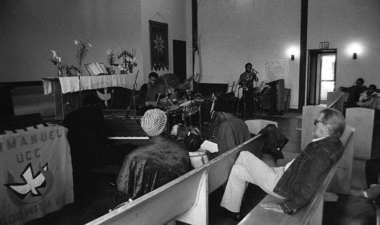 """Tom Albach at Pan Afrikan Peoples Arkestra last-Sunday-of-the-month concert at Immanuel United Church of Christ, Los Angeles -- April 26, 1981 -- w/ Horace Tapscott hunker'd down over the spinet and Fundi LeGohn, French-horn; Fritz Wise, drums: Linda Hill and JuJeGr sitting in front row -- photo by Mark Weber ---- Today (December 13, 2015) is Tom's 90th birthday, I just talked with him on the phone (he lives nearby in Albuquerque with his wife Pat), maybe not completely hale & hearty, but still full of piss & vinegar, having survived a couple bouts with cancer, he's on the mend, still reading his beloved Manchester Guardian (British) and Le Monde Diplomatique (French) for his political news, still smokes a little reefer """"a marvelous balm!"""" for his glaucoma, still walks an hour every morning, """"up here the air is so good! it's great to get out every morning!"""" still plays pool in the afternoons in his neighborhood (he was once a pool hustler, so don't engage him on the tables, even at age 90 he can take you), finds the current music scene in America not good, some of this new jazz sounds like it's made for 12 or 13 year-olds! It's infantile, music for kids! Just the fact that I sell more music over-seas in Europe and Japan gives you an indication where things are at, the fact that Trump has a following is indication how successful the Replublicans have been in stupifying the American people . . . . the trouble this country is in, whew, capitalism has turned us into monsters, we're cruel! And the music, the richness is gone, there's no dimension, it's all superficial and jive! I can't believe the young people became so corrupted, they think thier music is hip! I raised my prices! [laughter][see Nimbus West Records] ----- my favorite quote from him this morning: """"All these awards like Grammys and Emmys, they aren't awards, they're indictments!"""""""