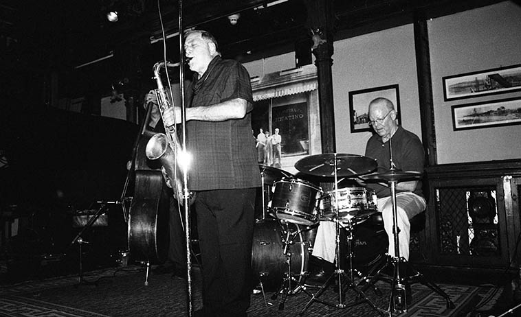 """Kazzrie Jaxen Quartet: Charley Krachy (tenor), Don Messina (bass), Bill Chattin (drums), Kazzrie Jaxen (piano) -- August 24, 2o14 -- photo by Mark Weber -- this music is purely honest, they will not put you on or emotionally manipulate you with grandstanding crescendos, or slow atmospheric long drawn-out build-ups of contrived appointments with a glorious payoff at the end, if you can wait it out (I guess that's what you call a crescendo, eh?) You'll not hear moaning & groaning from the pianist, histrionics, balderdash, psychological meltdowns from the stage, jive is foreign territory here, as is pretension, the drummer won't holler """"Yeh, man,"""" to the bass soloist signaling something mysterious has occurred but we in the audience are too unhip to know what just happened, this music brings you along with it or it just isn't happening, you have to be there, this music includes the listener, already there, already in the moment, as they say. Anything else is foreign to these artists."""