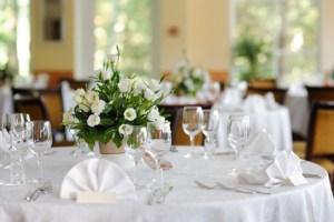 table de réception pour repas de mariages réception - joli bouquet au centre de la table de fleur blanches - serviette de table dressé en éventail -