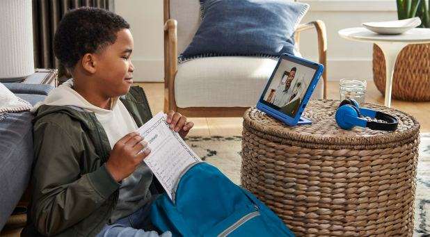 Boy seated on floor, taking papers out of backpack while watching video on tablet screen