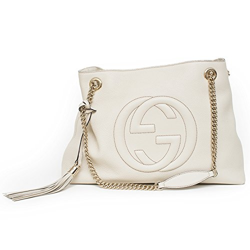 "A medium size Soho shoulder bag with double chain shoulder straps and an embossed interlocking G. Made in our light, natural grain leather in Ivory White. Light gold toned hardware Ivory Ivoire Off-white leather Detachable leather tassel Embossed interlocking GG Cotton linen lining Cotton linen lining Double chain shoulder straps with leather shoulder pad 7"" drop Inside hook closure Medium size: 15""W x 10.6""H x 5.5""D Made in Italy"
