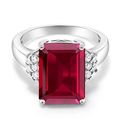 MEASUREMENTS: 14x10mm Emerald Cut Red Created Ruby, 2x2mm Round White Zirconia. Total Carat Weight is 8.30 cttw. CRAFTED: in 925 Sterling Silver with 925 stamp. USA BASED COMPANY AND SERVICE: Our jewelry passes extensive quality checkpoints before be...