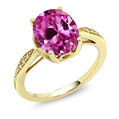 MEASUREMENTS: 10x8mm Oval Pink Created Sapphire, 0.7x0.7mm Round Single Cut I - J Diamond. Total Carat Weight is 3.29 cttw. CRAFTED: in 14k Yellow Gold with 14k stamp. USA BASED COMPANY AND SERVICE: Our jewelry passes extensive quality checkpoints be...