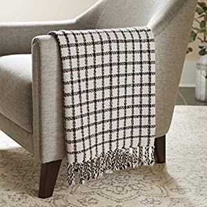 """Imported Add some simple sophistication to your living room comfort with this elegant throw blanket. The black and ivory grid creates a clean, eye-catching style, and a row of twisted tassels on either end complete this fun and versatile design. 60""""L..."""