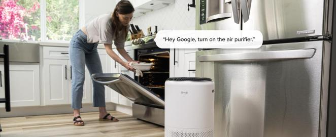 A woman uses a voice assistant to operate core400s while cooking