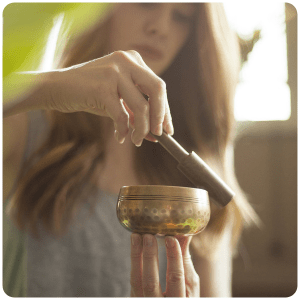 Nikki, co-founder of The Ohm Store holding an ancient design singing bowl by a fireplace