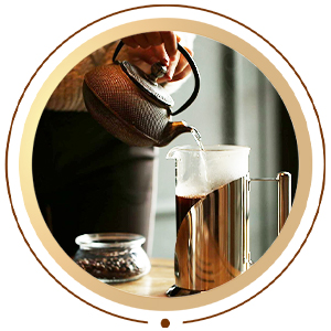 Person pouring hot water into coffee press glass carafe