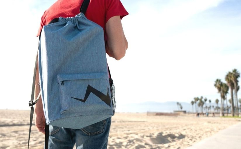 kids skateboard backpack held by a guy with red shirt by the beach with palm trees