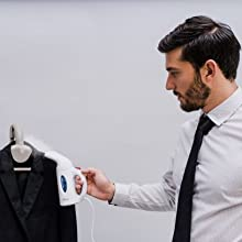man ironing steaming a suit
