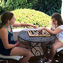 Girls playing WE Games Solid Wood Checkers Set with grooves outdoor sunshine green plants smiling