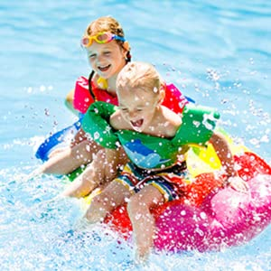 Kids playing on pool float in water - Neutrogena Wet Skin Sunscreen is formulated for active kids
