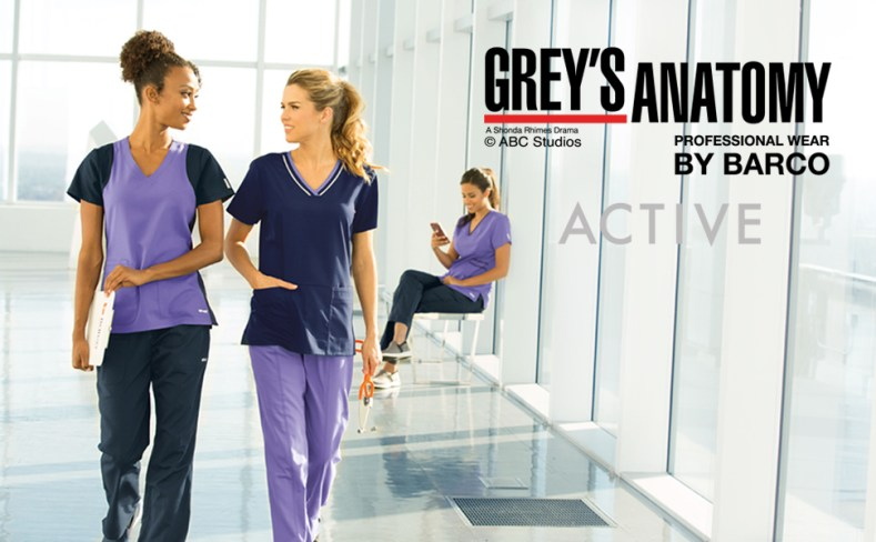 Two nurses chatting in hallway. Another one sits in the back on the phone, all wearing Barco Scrubs