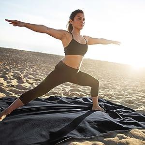 Girl doing yoga on waterproof outdoor blanket on the beach, sandproof weatherproof for outdoor use