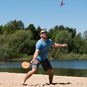 Man playing paddle ball at the beach under the sun having a fun time with jazzminton