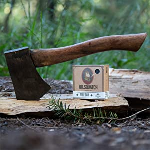 pine tar soap bar on wood log next to axe hatchet in the woods