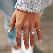 girl hand wearing rings and grey sweater