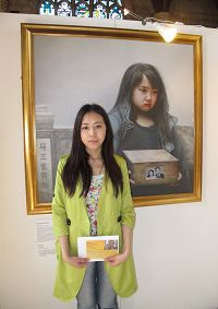 """'图4:于铭慧手里拿着营救父亲的明信片站在""""真善忍国际美展""""画作""""孤儿泪""""前'"""