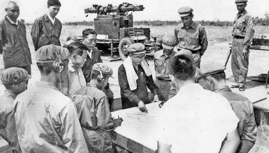 Khmer Rouge senior defence personnel look at a map during the 1970s