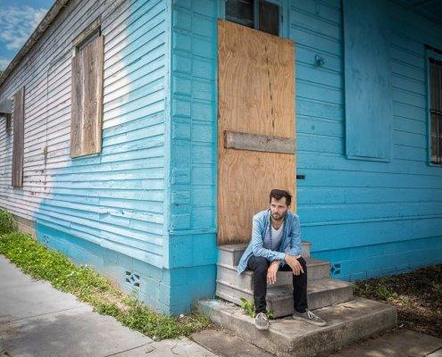 """Hugh Coltman devant une maison bleu pour la sortie de son album """"Who's Happy ?"""""""