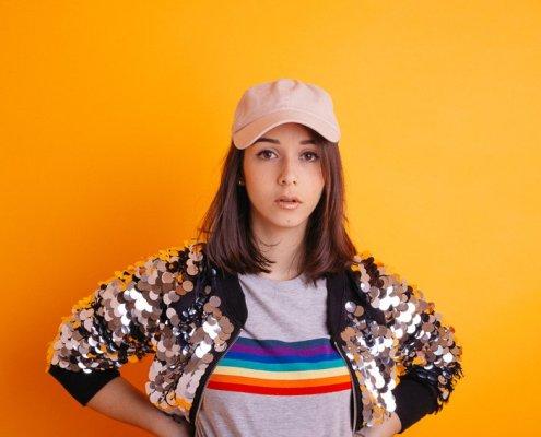 """Portrait sur fond orange de la jeune artiste Clarisse Mây pour la sortie de son EP """"Panache"""""""