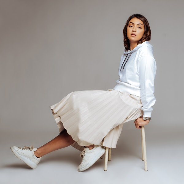 L'artiste féminine Yezza tout en blanc assise sur une chaise pour la promotion de son titre Gare du Nord