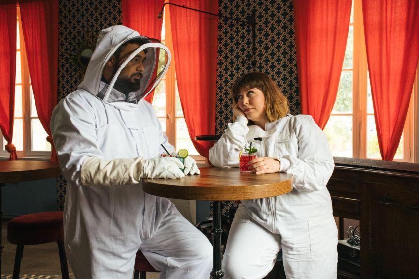 portrait du duo Part-Time Friends prenant un verre de soda en tenue d'apiculteur