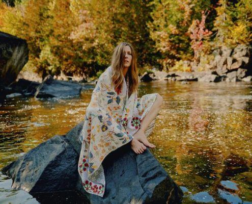 Portrait en extérieur de l'artiste BEYRIES assise sur une pierre sur un lac canadien