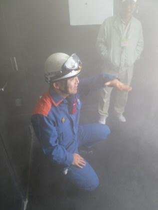 Palomies näyttää, että palavasta rakennuksesta tulee poistua matalana.