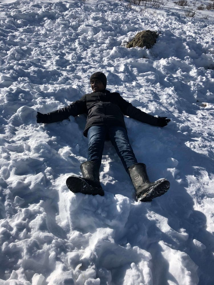 teenager enjoying making angels in the snow - experiences are more important than material joys